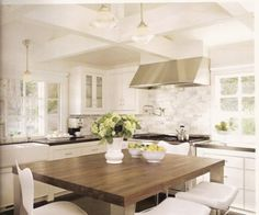 modern farmhouse kitchen.  marble + warm wood + white + ceiling beams | Tia Zoldan Interiors