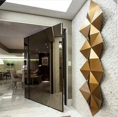 A mirrored pivoting door with metallic modern sculpture on entry wall.