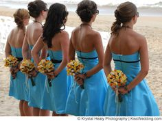 beach bridesmaids in bright blue dresses with orange and yellow bouquets.