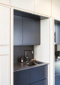 """""""Likaiset astiat sekunneissa piiloon Topi-keittiön keittiössä kaiken mahdollisen saa piiloon. Koivuviiluisten ovien taakse kätkeytyy niin trendikäs aamiaiskaappi kuin hieman yllättäen myös tiskiallas. Likaiset astiat on kiva saada hetkessä pois silmistä – ja ehkä myös mielestä. Kohde 6, Kannustalon Harmaja Saimaa."""""""