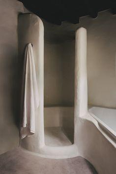 Minimalistic rustic bathrooms with a dreamy calm vibe in Ibiza, design by Hollie Bowden | Tadelakt bathroom, stucco bathroom, minimalist rustic bathroom, built-in bathtub, built-in shower, concrete bathroom, modern country bathroom, contemporary rustic bathroom