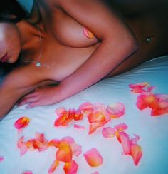 Sun kissed and bare skinned girl surrounded by orange rose petals