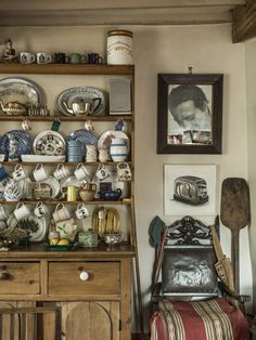 A pine dresser, which serves as Ormsby Gore's main kitchen cupboard, stands beside a bread paddle, an old chair, a painting of a toaster by the British artist John James and a photograph of Meher Baba, an Indian spiritual leader. (Photo: Martin Morrell)