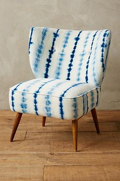 PATTERN' The tie-dye pattern on this chair shows a predictable repetition between the light blue and navy stripes moving vertically down the chair.