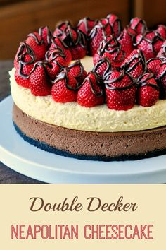 Double Decker Neapolitan Cheesecake - Our 1000th Recipe! A vanilla and a chocolate cheesecake in one, topped by fresh strawberries and a drizzle of chocolate ganache.