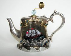 A tiny galleon in a 'Batchelor teapot' which goes round as you turn the handle. The ship is afloat on a sea of cracked blue glass, and decorative elements are all reclaimed. https://www.facebook.com/luxandlove