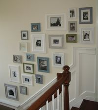 I like this... would even try in a hallway that did not have stairs :-).   Frames on stair wall: four quiet colours - white, gray, blue and green, with photos in all of them. frame wall by Sandra on her blog sawdustandpaperscraps