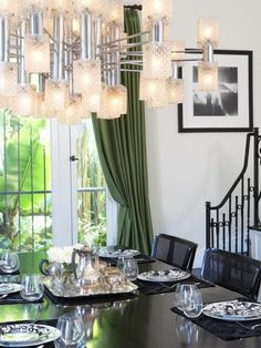 Dining Room: Dining Space With Black Dining Table And Trendy Chrome Finished Chandelier. black dining table. rectangular dining table. black dining chair. green curtain. glass window. chrome finished chandelier. black and white wall art. black placemat.