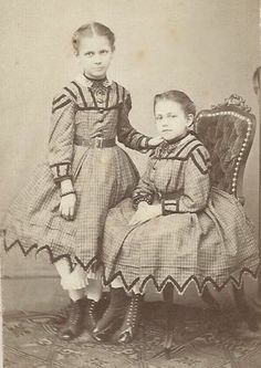 Outstanding Portrait of Two Young Girls Amazing Dresses Boots c1860s. Each has a few bracelets.