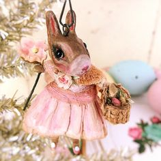 "What a wee sweet one Rose is!She holds a vintage floral in one paw and a basket of eggs in the other.  Her tiny cape is actually a velvet rose petal that was once part of an Easter hat.Head turnsVintage crepe paperGlass eyesHandmade crepe paper rose attached to her cape2 1/2"" tall"