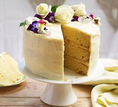 Elderflower & lemon celebration cake served on a cake stand and decorated with fresh flowers
