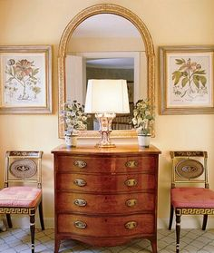 Symmetry. Architectural Digest. Antique dresser, pink velvet chairs, mirror, chic vignette, booth display antiques I like, color palette