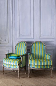Pair of Louis XVI Bergères covered in a Manuel Canovas striped velvet, against Louis XVI wood  paneled walls