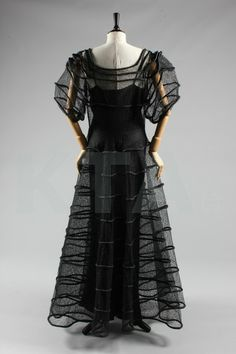 A black lace and rouleaux satin evening gown, attributed to Madeleine Vionnet, probably Spring-Summer, 1936 collection, with square neckline, full sleeves, the gossamer fine lace intersected by the padded silk bands, circular armholes cut out of the lace roundels of the sleeves. Back