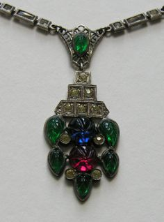 Art Deco Fruit Salad Sterling Necklace  This striking Art Deco necklace is done in the style of the very popular Cartier pieces of the period.  The necklace features colored molded glass fruit and leaves accented with clear pastes and filigree insets.