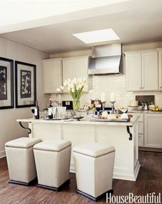 """A trio of backless stools can be slipped under the counter to save space, as in this tight Alabama kitchen, designed by Susan Ferrier. Their cream color blends in with the island, unifying the room. """"You don't want the eye to stutter in a small space,"""" she says.   - HouseBeautiful.com"""