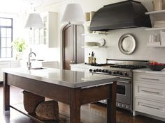 """White cabinets warmed rich woods, deep gray hood. Shown on  Greige Blog, from """"Atlanta Homes and Lifestyles"""" magazine"""