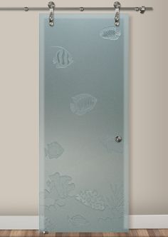 Interior Sliding Glass Barn Door featuring the Tropical Fish design in the 3D Enhanced Private effect by Sans Soucie Art Glass. Design elements are sandblast sculpted, cut deep into acid etch frosted glass at varying depths that create a relief texture and 3 dimensional effect in the design elements.  The acid etch frosted finish creates 100% obscurity in the glass. Sliding Glass Barn Doors, Glass Door, Name Design, Fish Design, Sand Glass, Glass Art, Art Deco Borders, Fan Coral, Lake Arrowhead