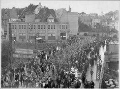 7. August 1914: Die Soldaten ziehen über die Herzogbrücke aus Kleve hinaus zum Bahnhof. Im Hintergrund sind das Krankenhaus (später Rathaus), die Spitze der Minoritenkirche sowie entfernt das B.C.-Koekkoek-Haus zu sehen.