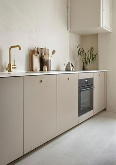 Kitchen with beige cabinets and brass details by Anna Pirkola. Photo by Katri Kapanen #vintagekitchendecorating
