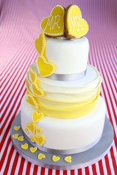 A decadent three tiered ruffle cake, with mellow yellow ombre detailing and fondant hearts cascading down the cakes exterior. Before being topped with biscuit 'Mr and Mrs' toppers! A perfect addition to any wedding party. Three Tier Cake, Ruffle Cake, Mellow Yellow, Tiered Cakes, Favours, Cake Ideas, Fondant, Food To Make, Biscuits