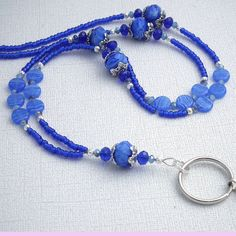 This beaded id badge lanyard is designed with beautiful deep cobalt blue lampwork beads set between lovely silver bead caps. Small blue and white