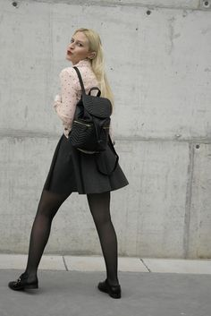 Black tights with pleated grey skirt and pink shirt with black dot pattern