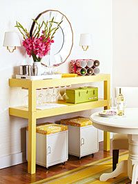 To construct this two-level buffet, start with a small rectangular dining table or desk. Cut the table in half lengthwise, cut the legs on one half to 12 inches tall, then paint both pieces. When dry, secure the bottom half to the wall using a wooden cleat. Stack the top piece on top; secure to the bottom section and to the wall.