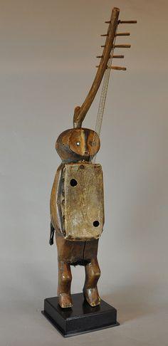 Cordófono pulsado Tipo: Arpa - República democrática del Congo - Cultura: Banda - Madera, piel, cristal, metal y fibras vegetales