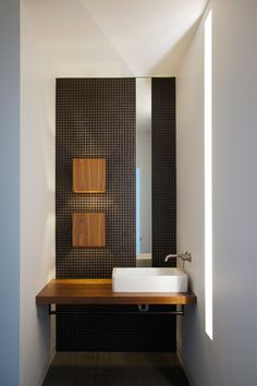Dark. mesh texture provides contrast in the room, and emphsizes the square vessel sink. Impact wall in the powder room with LED and natural lighting.