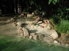 11. Natural play area. A small dug-out area filled with sand and bordered with natural stones makes an inviting play area for young children...
