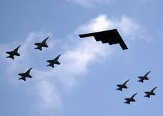 A U.S. B-2 Stealth bomber being escorted by U.S. Navy F/A - 18 Hornet fighter jets. PHOTO COURTESY: en.wikipedia.org