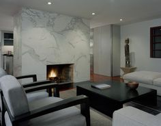 Contemporary living room with marble surround covering entire wall, no mantle.