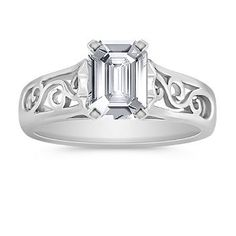 A Favorite, 6.9mm x 4.8mm Emerald cut White Sapphire  A contemporary take on a classic design, this 14 karat white gold engagement ring features a unique cut out design on the sides.  The center stone of your choice is the star in this bold design. Shown with a center stone Emerald Cut White Sapphire.