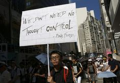 A protester holds a placard during a march in a downtown street in Hong Kong on Sunday to protest the upcoming introduction in schools of Chinese patriotism classes that they fear will lead to brainwashing. Teachers, parents, students and pro-democracy activists marched Sunday to the government headquarters of the semi-autonomous territory to protest against the new curriculum, which authorities are encouraging schools to begin using when classes resume in September.