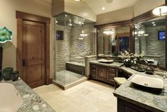 The stone of the countertops adds texture of this beige and dark wood master bathroom. The enormous corner shower stall includes a small window and a spacious bench. Three sets of mirrors follow the J-shaped line of vanities and makeup table. Elegant shallow vessel sinks up the wow-factor.