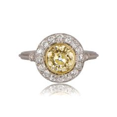 A graceful engagement ring featuring a beautiful fancy light yellow, SI1 clarity old European diamond. Surrounding the center diamond is halo of old European cut diamonds. The under gallery displays delicate and open work. Flanking the halo are one old cut diamonds along the shoulders. The mounting follows a triple wire design. The ring is entirely hand-crafted in platinum.  Diamond Weight: 1.38 carats Diamond Clarity: SI1 clarity Diamond Age: 1920s Ring Material: Platinum Certification: UGL…