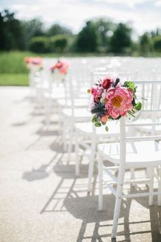 Floral chair markers for the ceremony add some color to white chairs. #weddingceremony #chairmarkers #flowers
