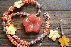 Vyrezávaný kúsok do tvaru kvetu z cherry kremeňa dopĺňajú tyčinky korálu s hnedými perleťovými kvetmi, filigránovými guľkami, brúsenými lososovými korálkami a perlami  Náušničky sú vyrobené z rovnakých materiálov.  Možnosť zakúpiť aj osobitne