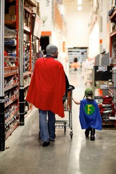 A father & son in matching superhero capes, browsing the aisles of Home Depot for supplies.