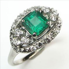 Oz: Ready for its Emerald City debut!  A stunning square cut emerald sits temptingly in the center of this mid-century diamond setting nestled closely with clusters of fiery diamonds. Ca 1950. Maloys.com