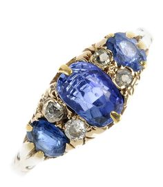 An early 20th century 18ct gold sapphire and diamond ring. The graduated oval-shape sapphires, with old-cut diamond double spacers, to the scrolling gallery. Weight 3.9gms.