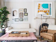 Living room with a fireplace, a gallery wall, and a pink ottoman
