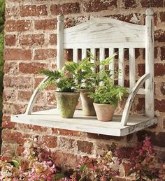 A chair with legs removed, crafted into a wall/plant shelf! Ingenious!
