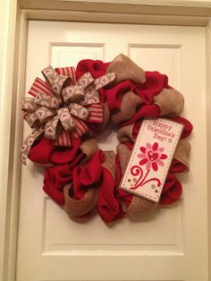 """Empire Wreath Co. """"Country Mod Sweetness"""" is approx 26 inches & about 8 inches deep (significantly less than the deco mesh wreaths & perfect for width limitations such as storm/screen door to front door space) with red burlap base, tan burlap garland, wooden with jute/burlap overlay 'Happy Valentine's Day' signage, and tan/red striped jute and tan with wht/red/pink heart printed double bow w/tails. $69."""
