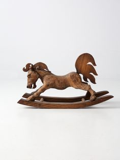 A one of a kind rare find! This wood folk art rocking horse was meticulously hand carved. The horse was crafted with a single block of wood, and is mounted atop a slender glider. Little wood handle ba