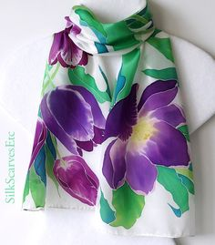 Step into spring wearing this floral hand painted silk scarf. This is a lightweight spring or summer scarf. I painted large purple tulips framed with green emerald and teal leaves on white background. This spring design is painted in softer colors yet its fresh and bold at the same time. The variety of greens and purple shades make it easy to match your outfits.  The scarf is 10.5 x 53.  Please see more of my handpainted floral scarves at https://www.etsy.com/shop/SilkScar...