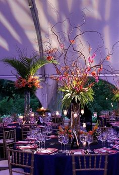 Willow branches colorfully decorated by orchid and gloriosa blooms and lit with hanging candlelight surrounded by low gold cubed bouquets of lilies and ferns.