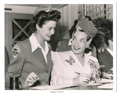 The Chevronettes were women signed up by Standard Oil Company to be part of the company's home front morale-raising and promotional war efforts. They were typically beauty queens and fresh-faced starlets who worked with celebrities to raise money during World War II. Here Chevronette Mary Ellen Gleason is seen with Carmen Miranda leading a war bonds drive at the Victory House on Pershing Square in Los Angeles in 1942.