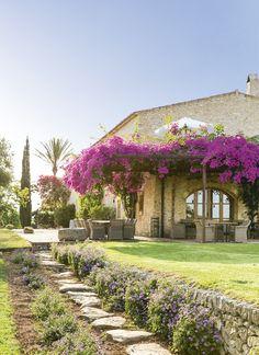 1 Vista del jardín y el edificio del hotel Son Gener, en Mallorca, con porche cubierto de buganvillas